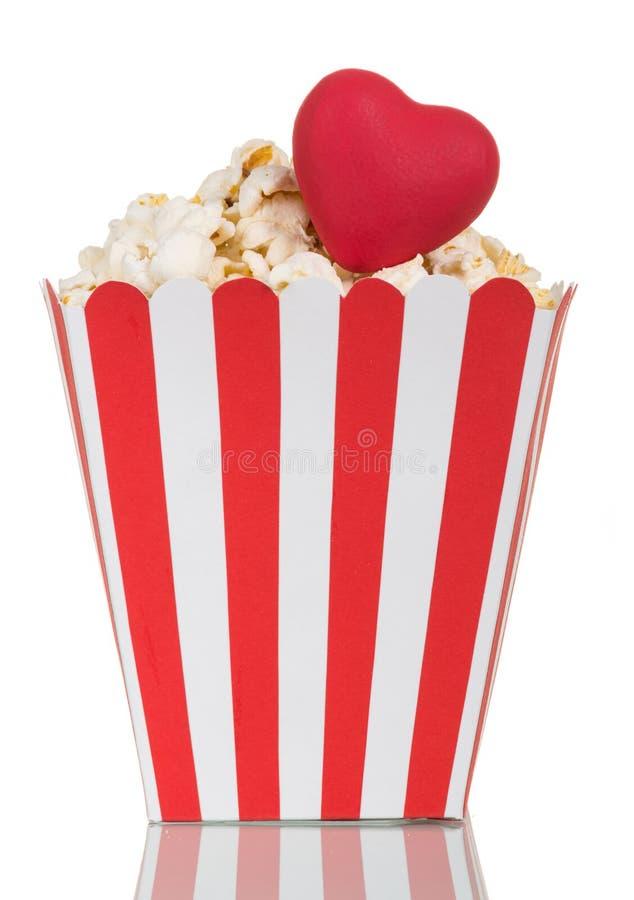 Popcorn σε ένα ριγωτό κιβώτιο εγγράφου και μια κόκκινη καρδιά που απομονώνονται στο λευκό στοκ φωτογραφίες με δικαίωμα ελεύθερης χρήσης