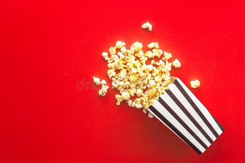 Popcorn στην τσάντα εγγράφου που διασκορπίζεται στο κόκκινο διάστημα αντιγράφων άποψης υποβάθρου τοπ στοκ φωτογραφία