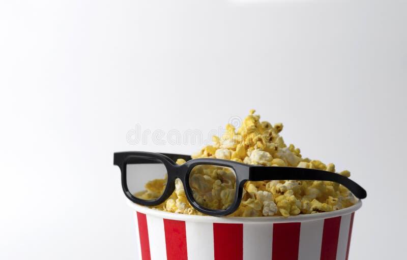 Popcorn στο ριγωτό κόκκινο κάδο με τα τρισδιάστατα γυαλιά στο άσπρο υπόβαθρο στοκ εικόνες