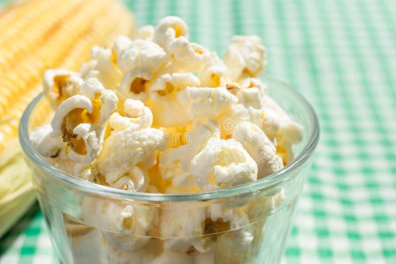 Popcorn auf Glasschüssel und grüner Tabelle des Plaids Lebensmittel von Festa Junin stockfotografie