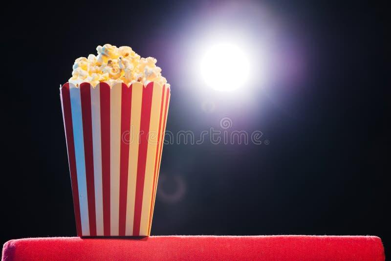 Popcorn ?ber Kinolichthintergrund, Filmkonzept stockfotos