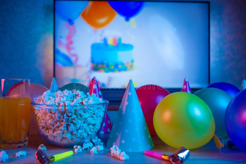 Popcorn birthday, party. On the background of TV and color bright light. Concept of festivals stock image