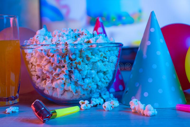 Popcorn birthday, party. On the background of TV and color bright light. Concept of festivals. Food celebration event delicious colorful tasty decoration royalty free stock photo