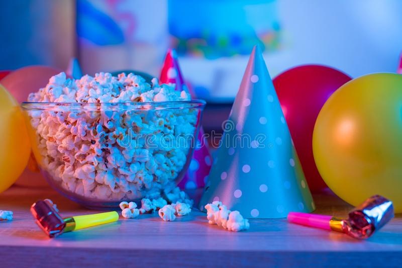 Popcorn birthday, party. On the background of TV and color bright light. Concept of festivals. Food celebration event delicious colorful tasty decoration stock images