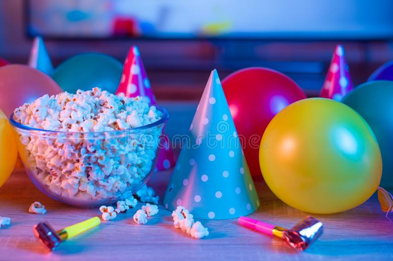 Popcorn birthday, party. On the background of TV and color bright light. Concept of festivals. Food celebration event delicious colorful tasty decoration royalty free stock image