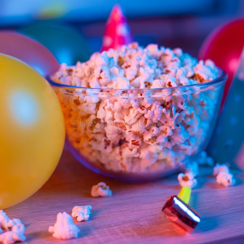 Popcorn birthday, party. On the background of TV and color bright light. Concept of festivals. Food celebration event delicious colorful tasty decoration royalty free stock photography