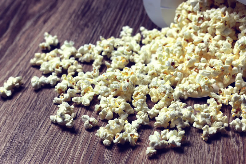 Popcorn box floor. A scattering of popcorn on the wooden floor while watching a movie stock images