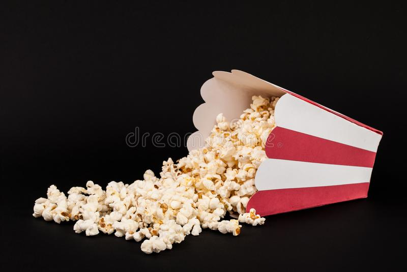 Popcorn box spilled on black background. Red and white box of popcorn spilled and isolated on black background. Movie and Food concept. Studio shoot royalty free stock image