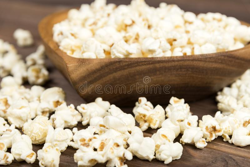 Popcorn in a brown wooden plate in the shape of a heart on a wooden table. Popcorn is laid out on the table royalty free stock photo