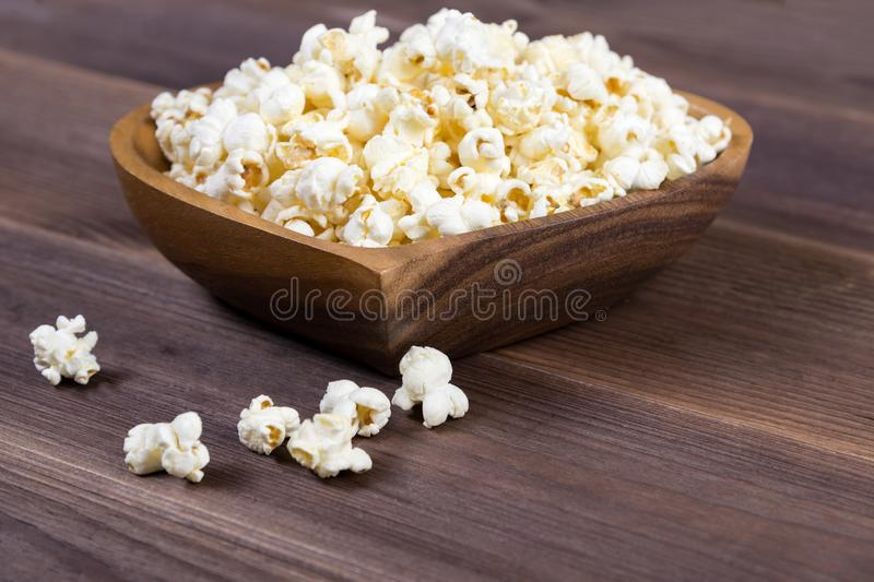 Popcorn in a brown wooden plate in the shape of a heart on a wooden table. Popcorn is laid out on the table.  royalty free stock images
