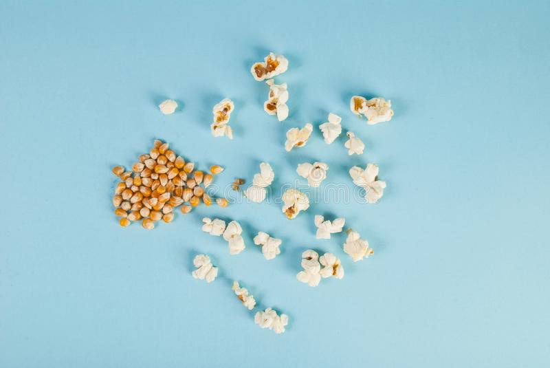 Popcorn and corn seed spilled on blue background. Food concept and idea image royalty free stock photo