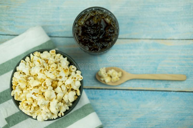 Popcorn in cup bowl with soft drink on wooden background. Top view stock image