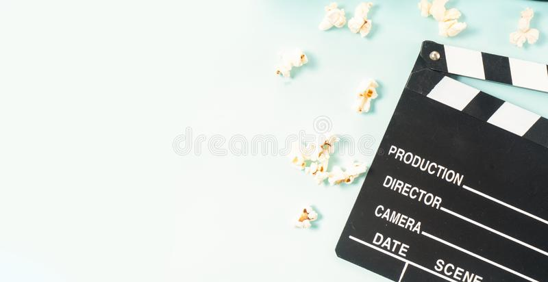 Popcorn and 3d glasses. Cinema clapper and popcorn over blue background, movie and cinema concept banner format royalty free stock photo