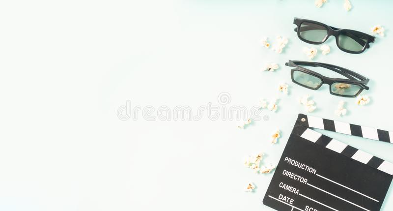 Popcorn and 3d glasses. Popcorn, cinema clapper and two pairs of 3d glasses over blue background, movie and cinema concept banner royalty free stock photo