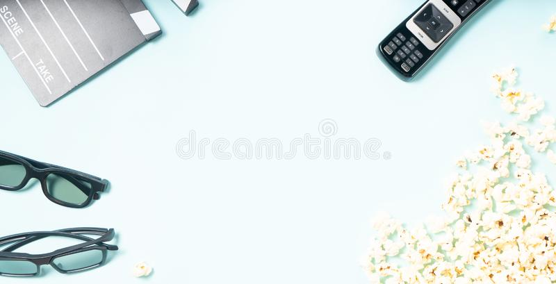 Popcorn and 3d glasses. Popcorn, cinema clapper and two pairs of 3d glasses over blue background, movie and cinema concept, top view banner format stock photo