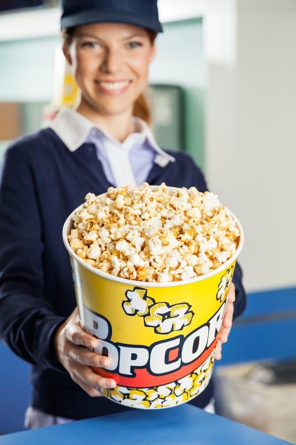 Popcorn d'offerta del lavoratore felice alla concessione del cinema immagini stock