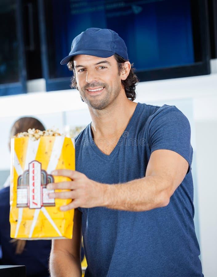 Popcorn d'offerta sorridente del lavoratore maschio alla concessione fotografia stock libera da diritti