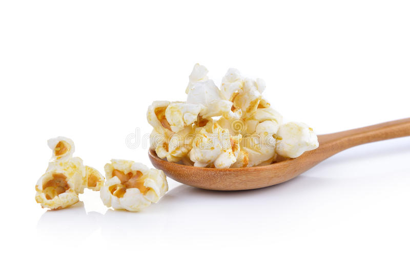 Popcorn in de houten die lepel op witte achtergrond wordt geïsoleerd stock foto's