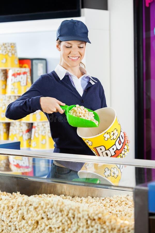 Popcorn del servizio del lavoratore in secchio al cinema fotografia stock libera da diritti