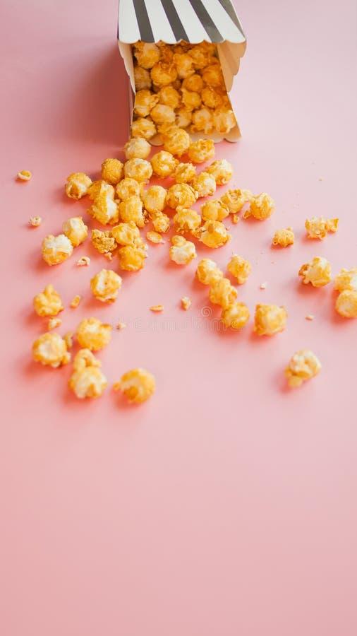 Popcorn in der Papiertüte zerstreut auf Draufsicht des Rosahintergrundes stockbild