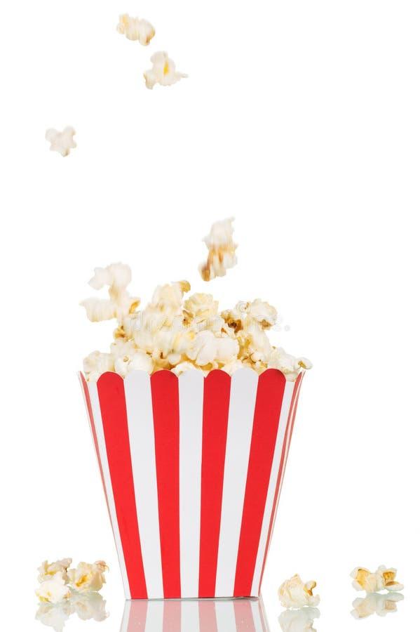 Popcorn di caduta in grande scatola quadrata ed accanto lei, su bianco fotografia stock