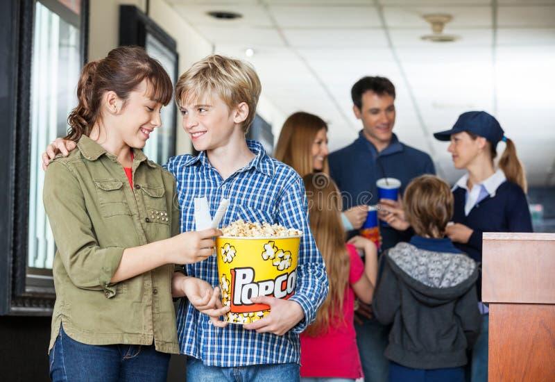 Popcorn di And Sister Holding del fratello al cinema fotografie stock libere da diritti