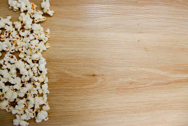 Popcorn die op houten achtergrond wordt geschikt stock afbeeldingen