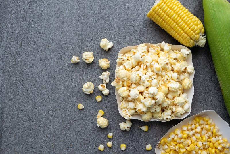 Popcorn in document kop met ruw graan op concrete lijstachtergrond royalty-vrije stock foto