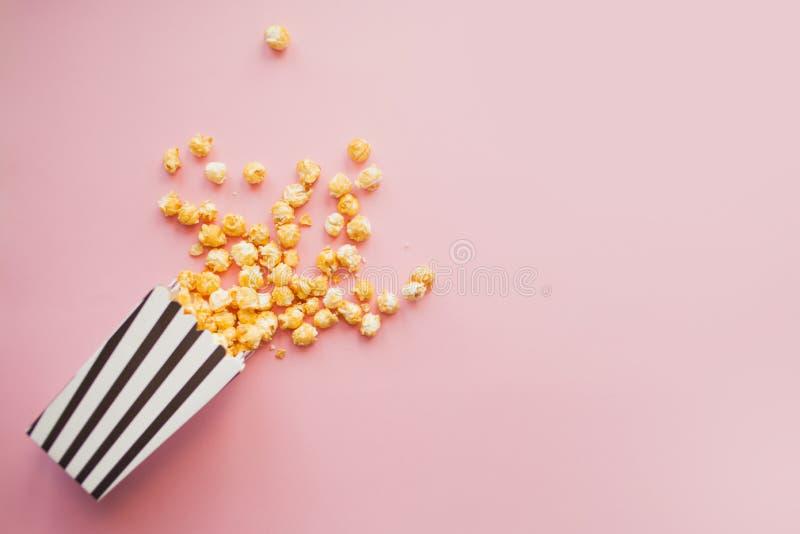 Popcorn in document zak die op roze hoogste mening wordt verspreid als achtergrond royalty-vrije stock afbeeldingen