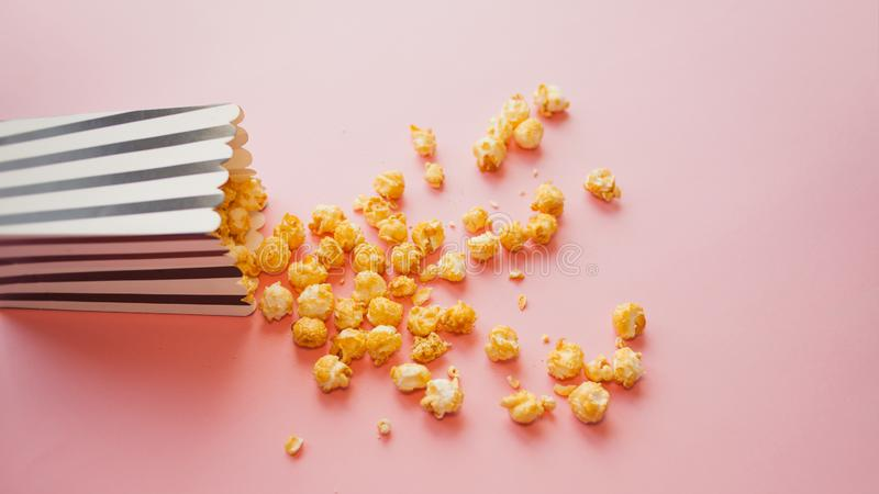 Popcorn in document zak op roze hoogste mening wordt verspreid die als achtergrond royalty-vrije stock afbeeldingen