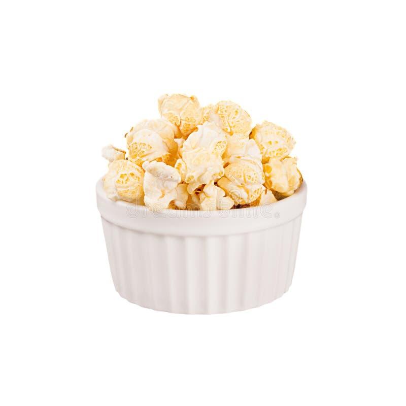 Popcorn dorato con nella ciotola bianca della ceramica isolata su fondo bianco immagine stock
