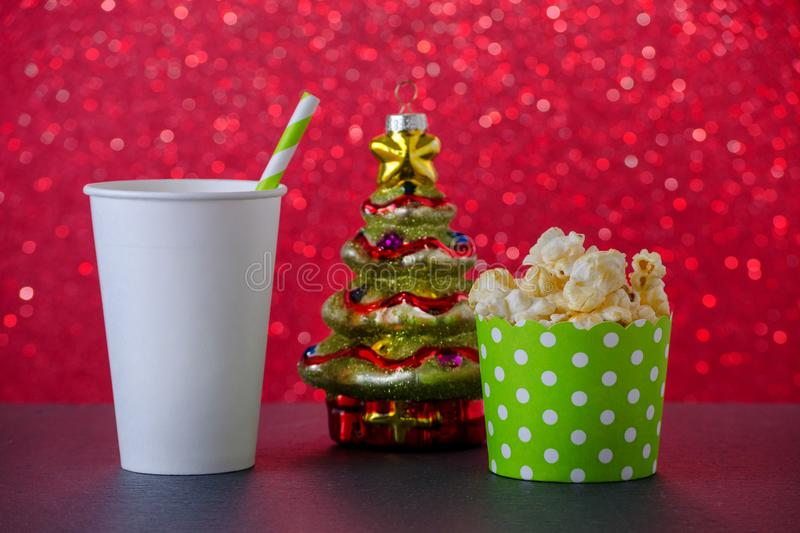Popcorn, drink and christmas tree decoration for movie on red bokeh background, selective focus stock photography