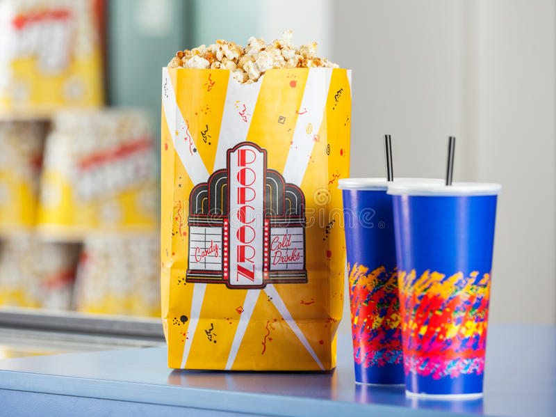Popcorn And Drinks On Concession Stand. Popcorn paperbag and cold drinks on concession stand at cinema stock image