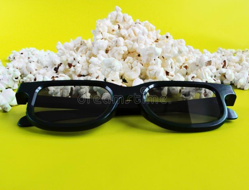 Popcorn en 3d glazen op gele achtergrond Conceptentijdverdrijf, vermaak en bioskoop stock afbeelding