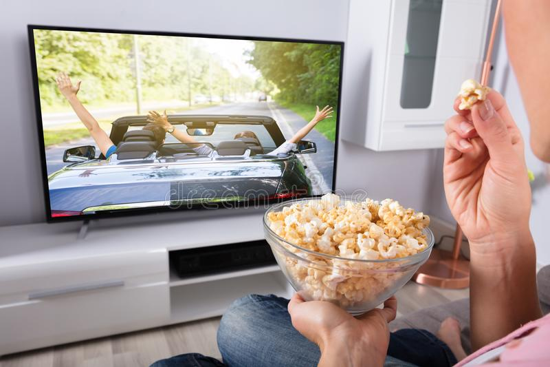 Popcorn för hand för person` s hållande, medan filmen spelar på television arkivfoto