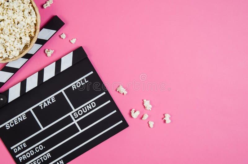 Popcorn, filmklem op roze hoogste mening als achtergrond, exemplaarruimte royalty-vrije stock foto's