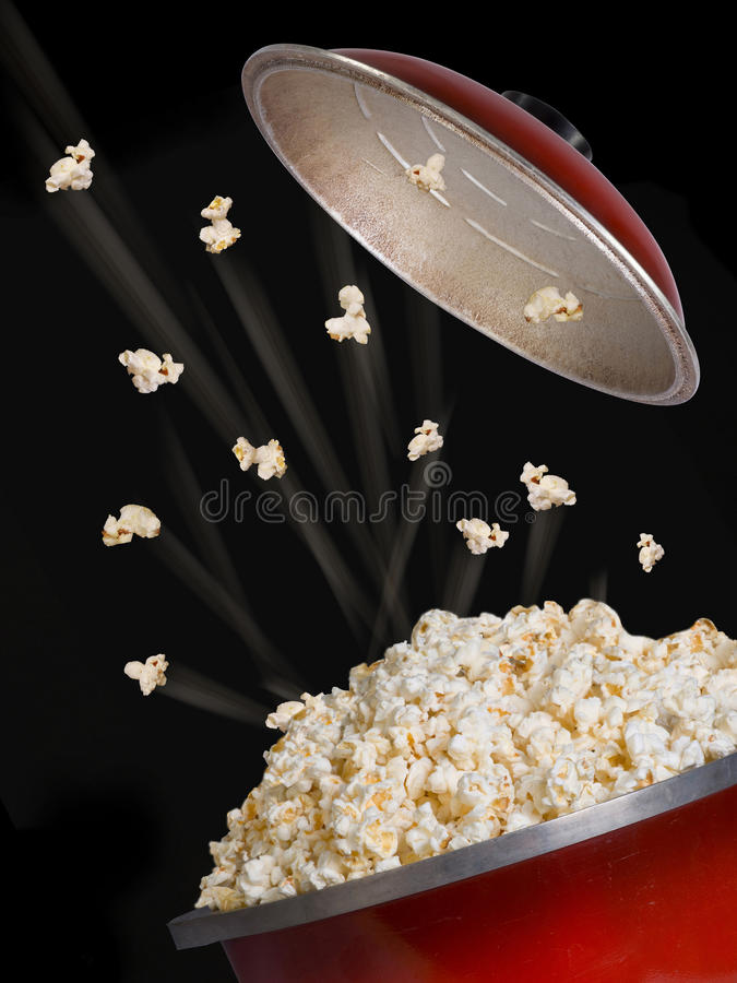 Popcorn Flying. Popcorn flying and exploding from red kettle royalty free stock image