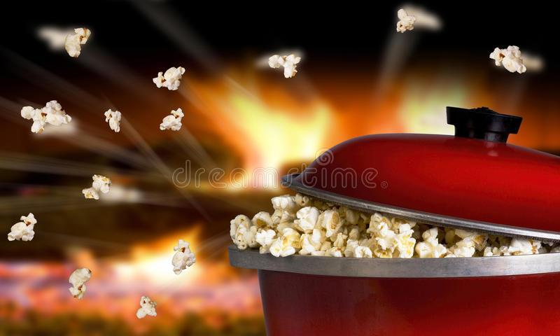 Popcorn Flying. Popping popcorn the old fashion way in a red iron pot stock photography