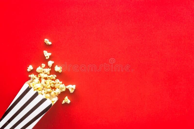 Popcorn i den pappers- påsen spridd på rött utrymme för kopia för bästa sikt för bakgrund royaltyfri fotografi