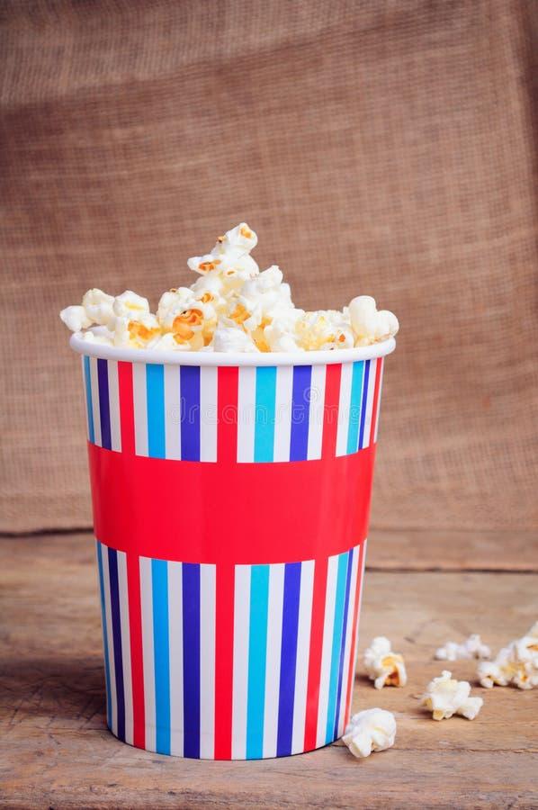 Popcorn i pappers- kopp på träyttersida royaltyfria foton