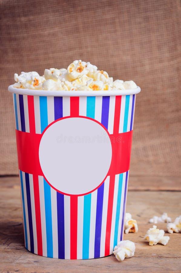 Popcorn i pappers- kopp på träyttersida kopiera avstånd royaltyfri fotografi