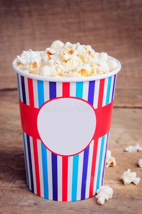 Popcorn i pappers- kopp på träyttersida kopiera avstånd royaltyfri bild