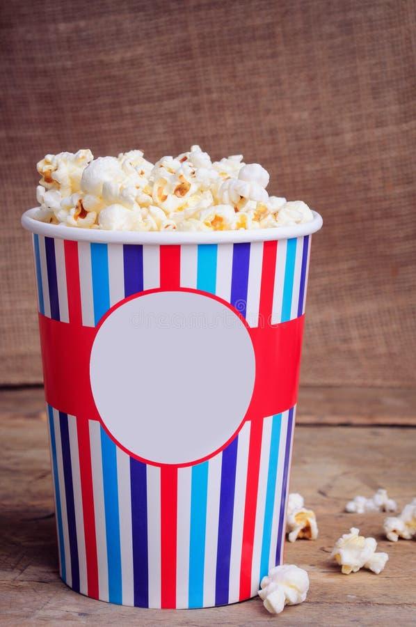 Popcorn i pappers- kopp på träyttersida kopiera avstånd royaltyfria bilder