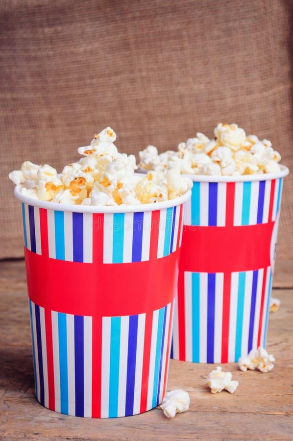 Popcorn i pappers- koppar på träyttersida arkivbild