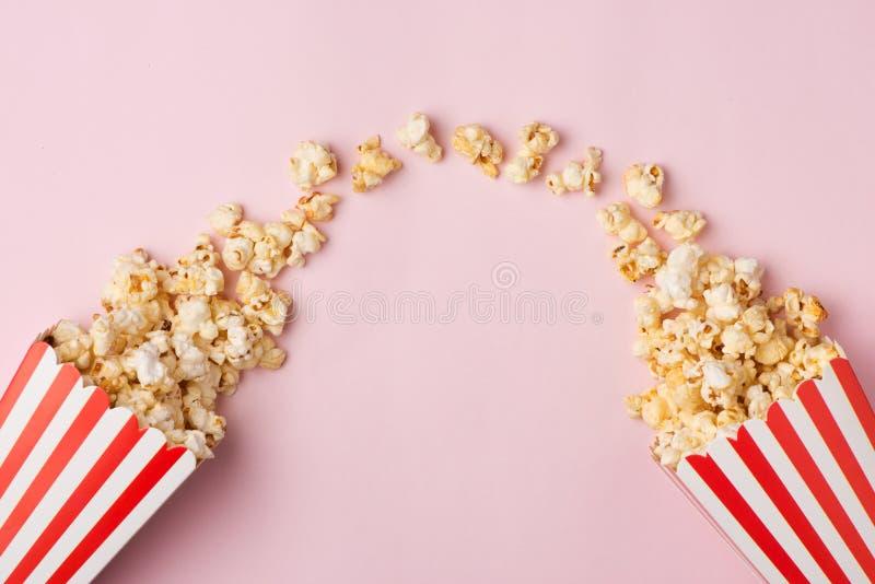 Popcorn i röd och vit kartong på den rosa bakgrunden fotografering för bildbyråer