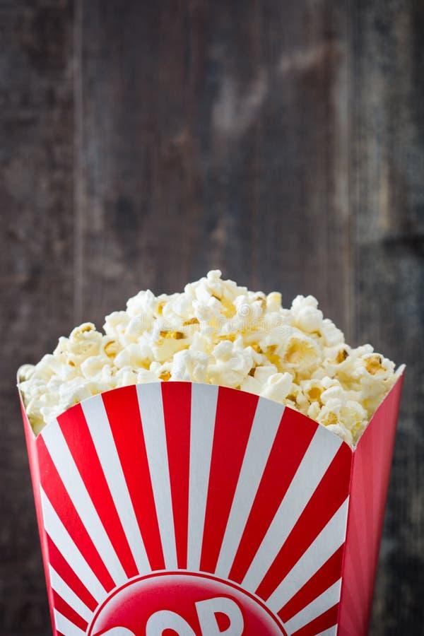 Popcorn inom förpacka som göras randig på trä royaltyfri foto