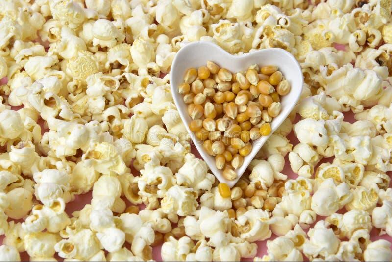 Popcorn inside heart bowl on pink background stock image