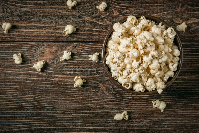 Popcorn in kom op oude houten achtergrond stock foto's