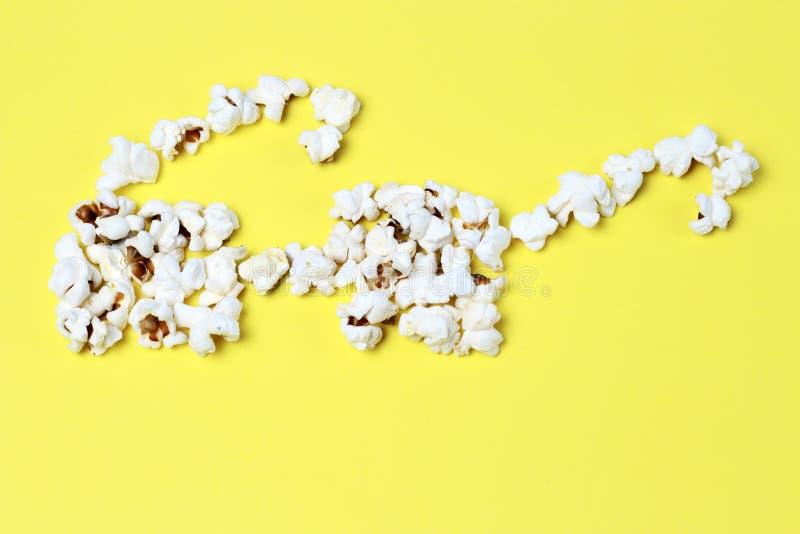 Popcorn lade ut i form av exponeringsglas på en gul bakgrundsnärbild, bästa sikt royaltyfri foto