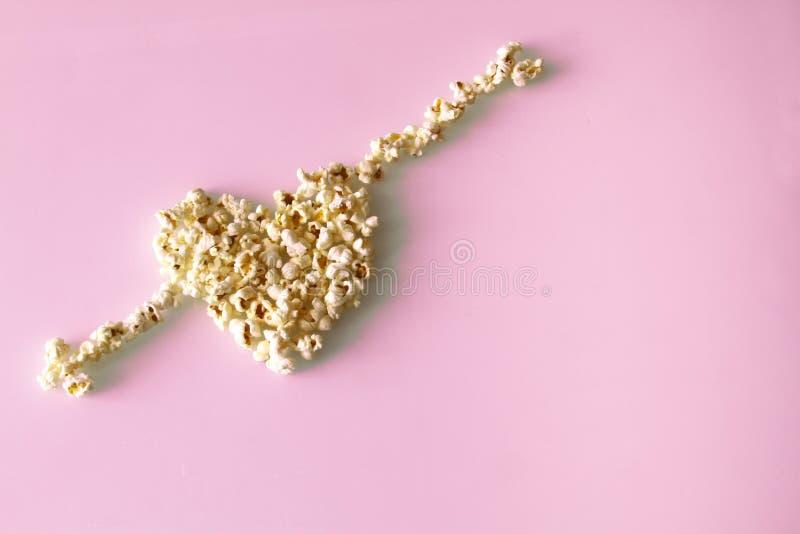 Popcorn lade ut i formen av en hjärta och pilar, på en rosa bakgrund royaltyfri bild